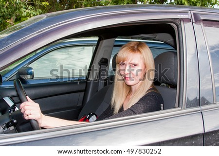Young woman sitting behind the wheel of a car