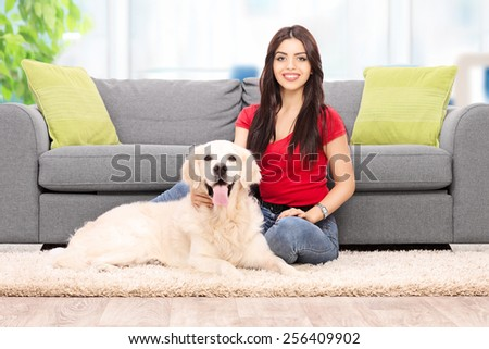 Young woman sitting by a sofa with her dog at home  - stock photo