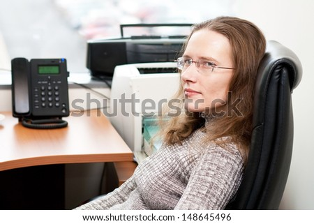 Young woman sitting by the office table