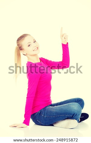 Young woman sitting cross legged and pointing up.  - stock photo