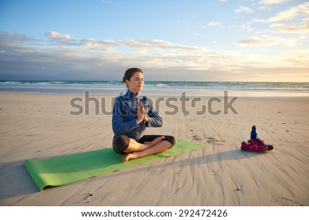 Young woman sitting cross-legged on her yoga-mat on the beach meditating at sunrise - stock photo