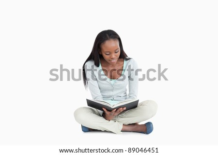 Young woman sitting cross-legged on the floor reading against a white background - stock photo