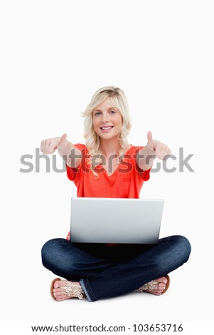 Young woman sitting cross-legged with her thumbs up against a white background - stock photo