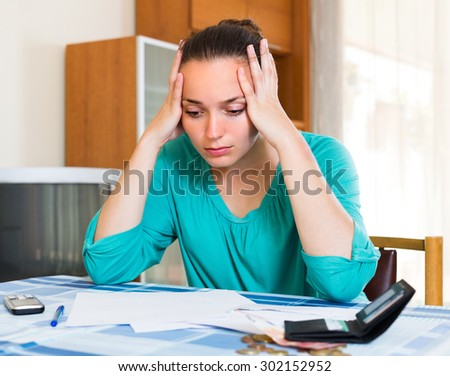 Young woman sitting depressed at the table because of bills 