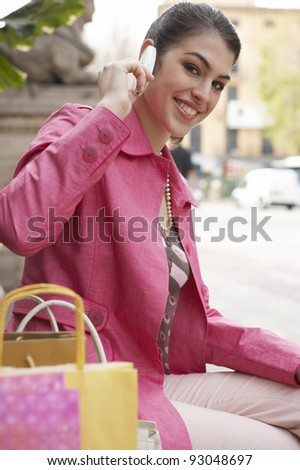 Young woman sitting down on a bench with her shopping bags, using a cell phone. - stock photo