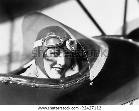 Young woman sitting in a biplane with hat and gargles - stock photo