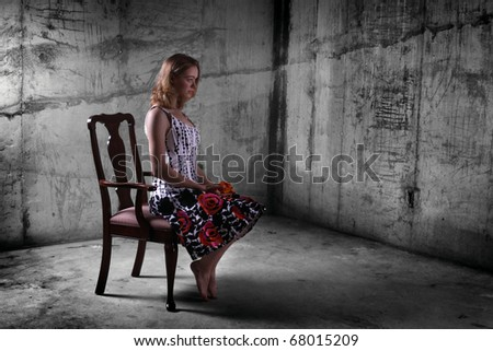 Young woman sitting in a chair in a dungeon-like setting. - stock photo