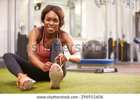 Young woman sitting in a gym tying her shoelaces - stock photo