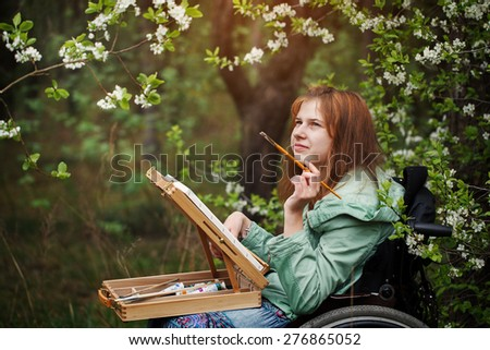 Young woman sitting in a wheelchair , smiling and painting on small easel. Spring day. - stock photo