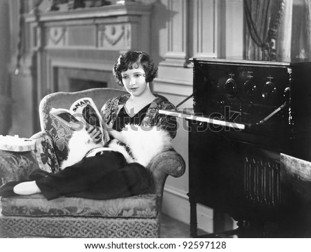Young woman sitting in an armchair reading a magazine next to a radio - stock photo