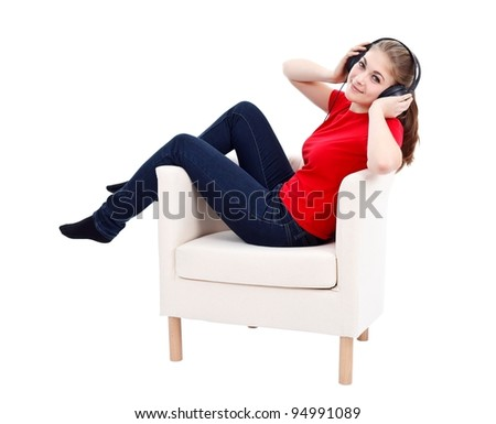 Young woman sitting in armchair with headphones, listening music - stock photo