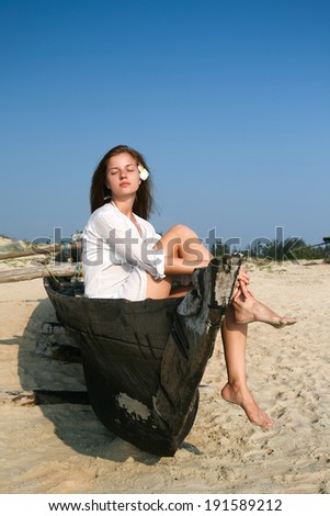 Young woman sitting in  black wooden boat  - stock photo