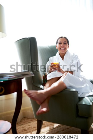 Young woman sitting in chair with legs over chair arm holding glass of orange juice. - stock photo