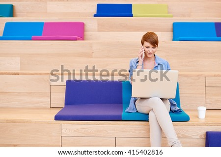 Young woman sitting in colourful space with laptop and phone - stock photo