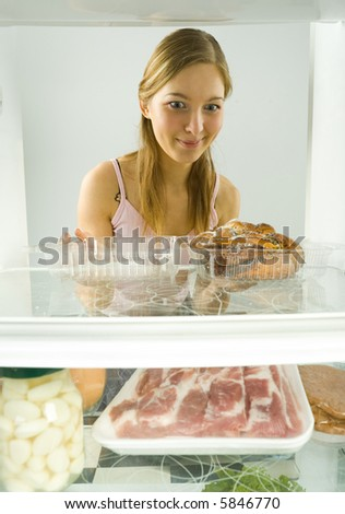 Young woman sitting in front of the fridge. Looking at sweet bun. Front view.