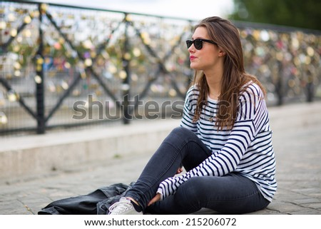 Young woman sitting in front of thousands of locks hung up at the side of a bridge in Paris, capital of France, as a sign of eternal love - stock photo