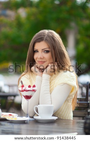 young woman sitting in outdoor cafe tasting dessert