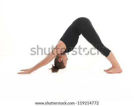 young woman sitting in stretching yoga pose, dressed in black, on white background - stock photo