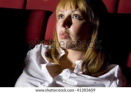 Young woman sitting in the cinema and watching a move - stock photo