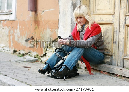 young woman sitting in the street and sending sms