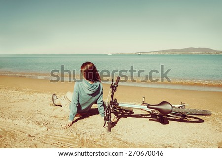 Young woman sitting near a bicycle on beach in summer - stock photo