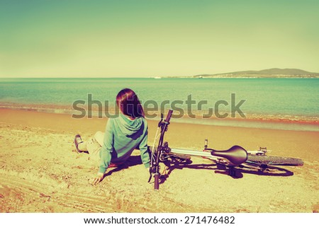 Young woman sitting near a bicycle on beach in summer. Image with instagram filter - stock photo