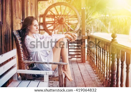 Young woman sitting near bungalow beach resort, enjoy and relaxing. Summer sea vacation, sunrise  - stock photo
