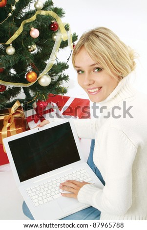 young woman sitting near christmas tree and gift with laptop, isolated on white background
