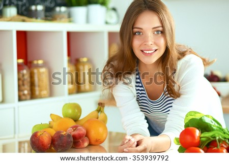 Young woman sitting near desk in the kitchen - stock photo