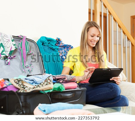 Young woman sitting  near overloaded suitcase while using digital tablet on sofa - stock photo