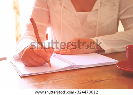 young woman sitting near window and writing. retro filtered image. photograph with natural window light . sekective focus - stock photo