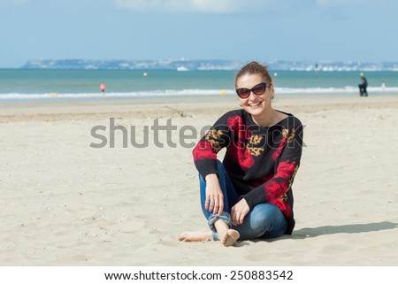 Young woman sitting on a beach - stock photo