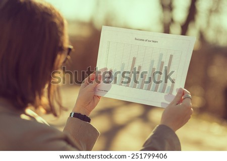 Young woman sitting on a bench in a park, analyzing data - stock photo