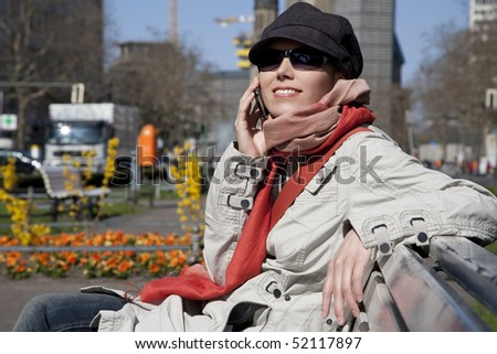 Young woman sitting on a bench in the park and talking on the cell phone