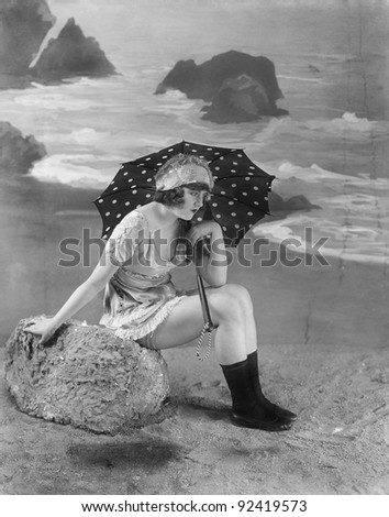 Young woman sitting on a bolder on the beach, holding an umbrella - stock photo