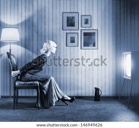 Young  woman sitting on a chair in vintage interior  and watching retro tv. She is very astonished while watching tv in dark room  - stock photo