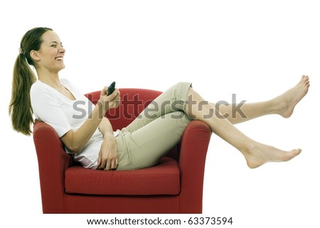 Young woman sitting on a chair with a remote control on white background studio - stock photo