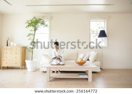 Young woman sitting on a couch and reading a magazine - stock photo