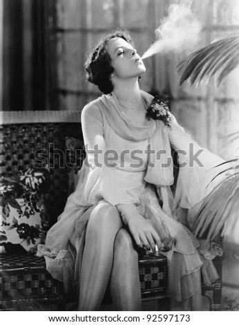 Young woman sitting on a couch smoking a cigarette - stock photo