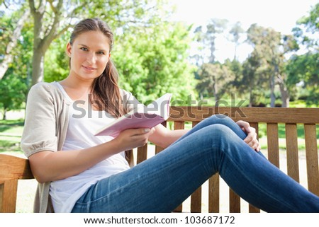 Young woman sitting on a park bench with a book