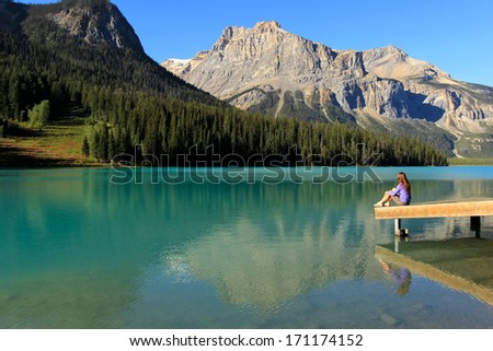 Young woman sitting on a pier at Emerald Lake, Yoho National Park, British Columbia, Canada - stock photo