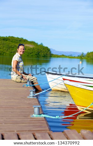 Young woman sitting on a pier. Lake in Asbyrgi area of Jokulsargljufur National Park of Iceland