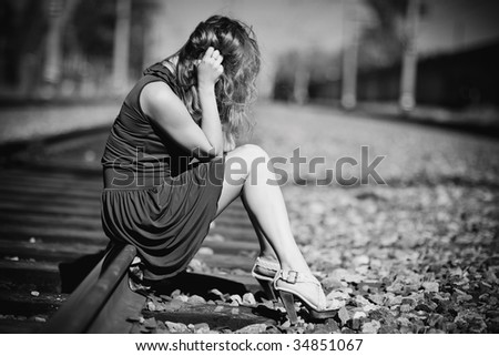 Young woman sitting on a rails. Sadness concept.