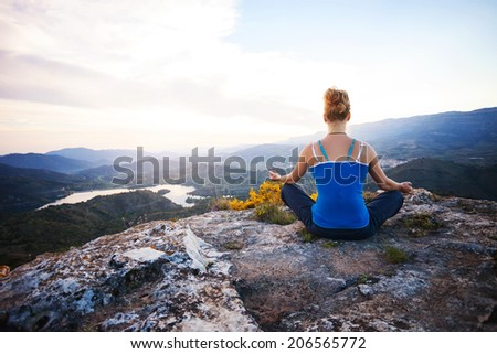 Young woman sitting on a rock and enjoying valley view. Girl sits in asana position.  - stock photo