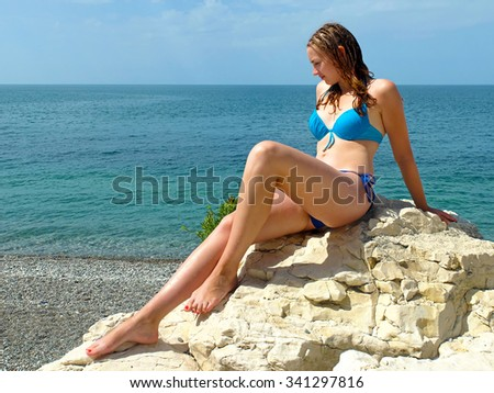 Young woman sitting on a rock, at sea