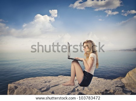 Young woman sitting on a rock over the sea and using a laptop - stock photo
