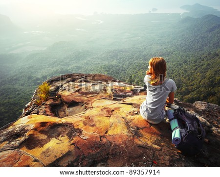 Young woman sitting on a rock with backpack and looking to the horizon - stock photo