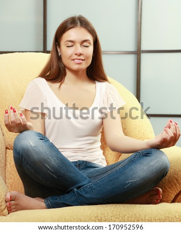 Young woman sitting on a sofa in the lotus position meditating