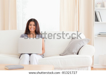 young woman sitting on a sofa with a notebook on her lap in the living room - stock photo