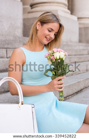 young woman sitting on a step holding a bunch of flowers
